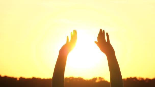 Dívčí ruce se pomalu kymácejí zblízka, chytají vítr na pozadí krásného západu slunce.