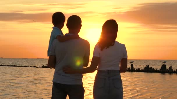 Happy family: father, mother and child enjoy a beautiful sea sunset. The woman hugs the man and puts her head on his shoulder. A father holds his son in his arms.