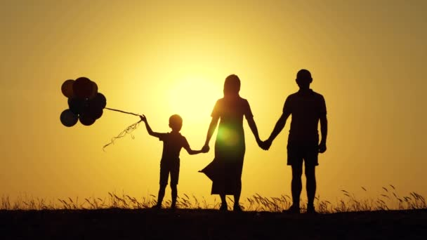 Silhouette of a happy family at sunset. Dad, mom and baby hold hands and look at each other.