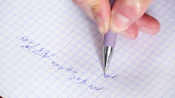Die Hand hält einen Stift und schreibt eine mathematische Formel in ein Notizbuch. Lösung der Gleichung. Das Konzept von Bildung und Forschung.