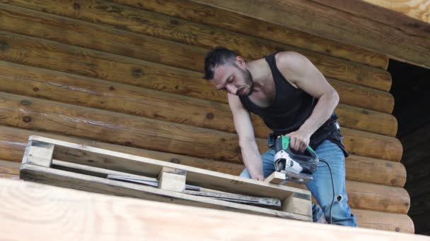 View from below. A young carpenter works with an electric jigsaw.