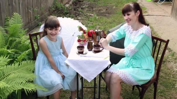 Máma a dcera sedí u stolu s ovocem a čajem.
