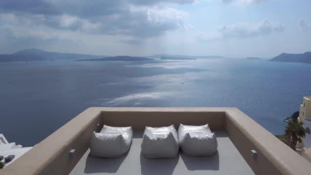 Nabílené domy a kostel na úpatí útesů s výhledem na moře a lehátka v Oia Santorini, Kyklady, Řecko