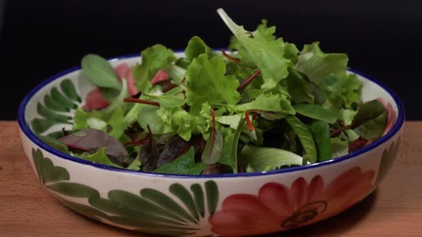 Mix salát spadá na zelené pozadí, pomalý pohyb