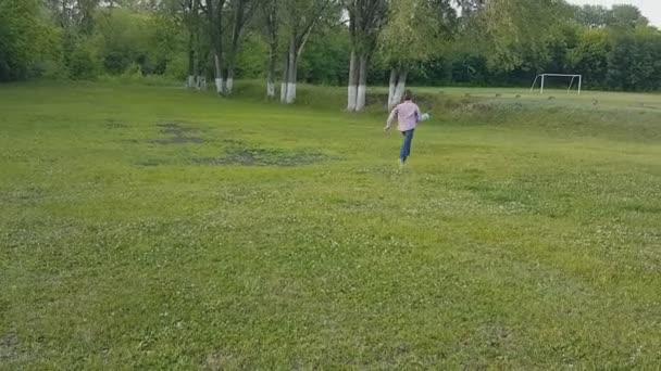 chlapec v džínách a kostkovanou košili hrát míč v parku na trávě v létě.