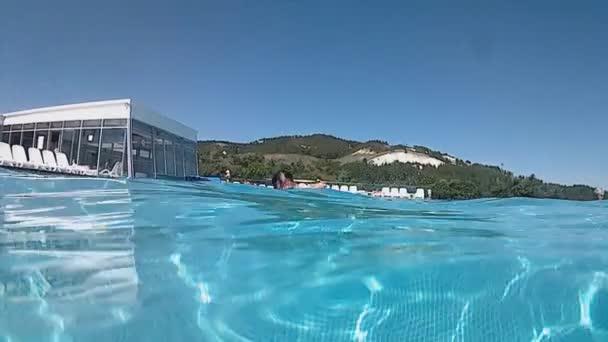 Bělošský vousatý muž plavání pod vodou v bazénu pod širým nebem za jasného slunečného letního dne. video byl zastřelen na akční kamery.