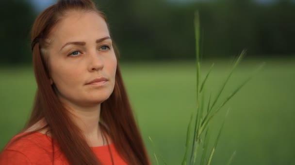 1c4c6b68fdab Mladá krásná žena s rudými vlasy stojí večer v poli s zelené pšenice a drží  uši pšenice v jejích rukou. Jednota s přírodou– stock záběr