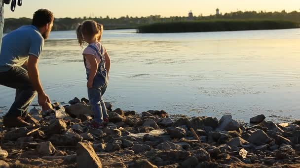 bearded father with a little girl sitting by the river and throw stones into the water on a summer evening at sunset.