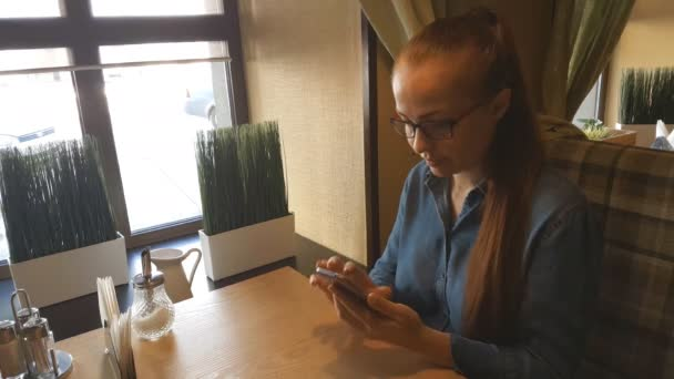 a beautiful Caucasian woman is a middle-aged businessman with red hair and glasses sitting with a smartphone in her hand in a cafe at a table.
