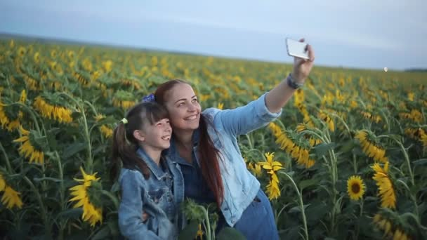 a beautiful Caucasian woman with red hair with her daughter take a selfie on her smartphone in the evening at sunset in a field with sunflowers.