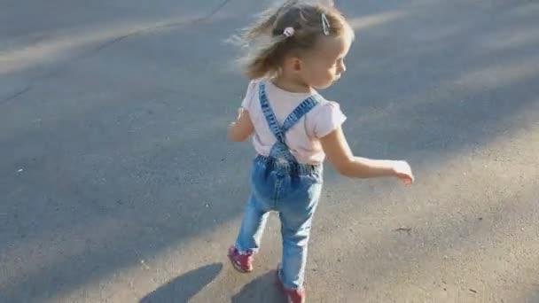 Kavkazské holčička s candy v ruce na tyčce běhá po parku v letním dni