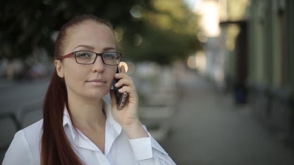 egy üzleti kaukázusi középkorú nő, vörös hajú, optikai szemüveg és egy fehér blúz teszi egy fontos hívást, míg a város utcában.