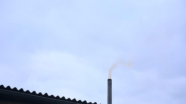 Kouř vychází z komína domu. Potrubí na střeše. Dům s komínem. Kouř na modré obloze.