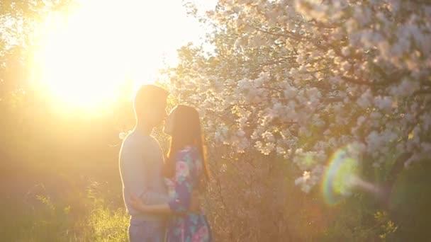 Loving boyfriend and girl in the summer garden at sunset
