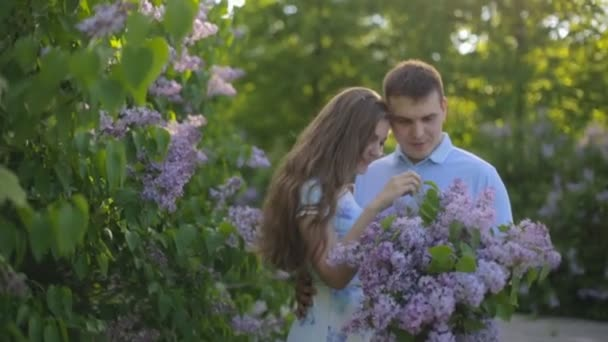 Loving guy and girl with a bouquet of lilac in the summer garden at sunset
