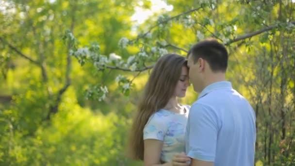 Liebender Kerl und Mädchen im Sommergarten bei Sonnenuntergang