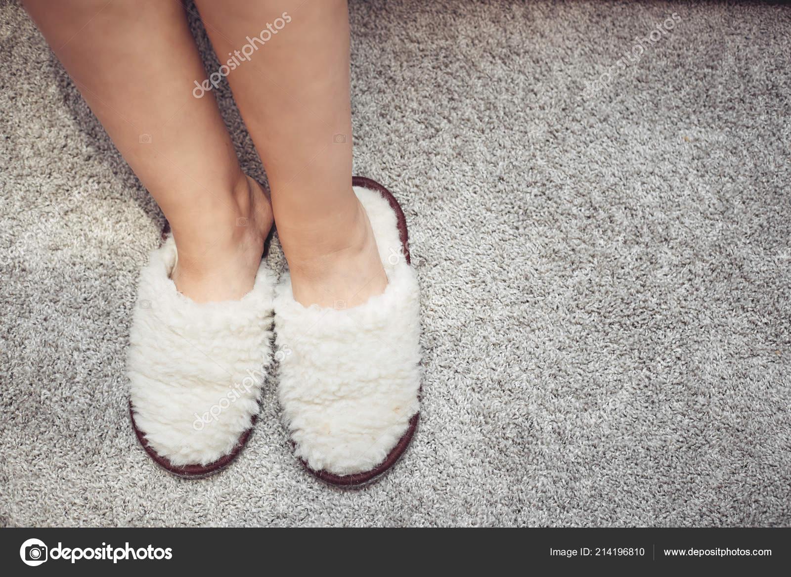 e61bf10dc98ba Womens feet in fur Slippers on a warm carpet. — Stock Photo © vadiar ...