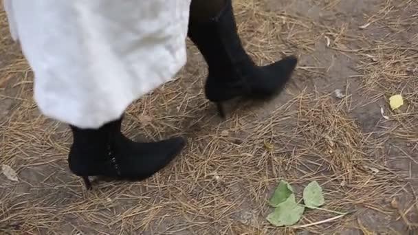 Dámské nohy v podzimní boty semiš a černé punčocháče na pozadí cesty Park
