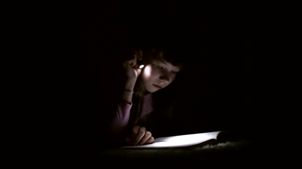 little girl is reading a book with a flashlight in a dark room at night