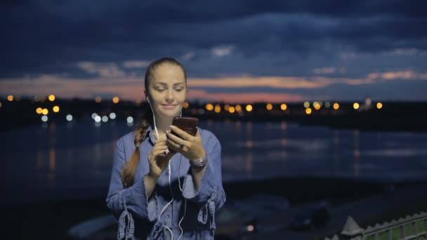 Porträt der jungen schönen kaukasischen Frau mit Smartphone-Hand halten in der Stadt-Nacht im freien Lächeln, Gesicht beleuchteten Bildschirm - soziales Netzwerk, Technologie, Kommunikation Konzept