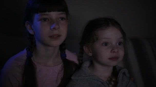two sisters watch cartoons on the computer late at night in a dark room