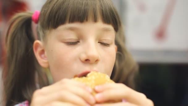 junge glückliche Teenager essen leckeren Hamburger in Fast-Food-Restaurant. Teenager-Mädchen isst Pommes zum Abendessen im Fast-Food-Café.
