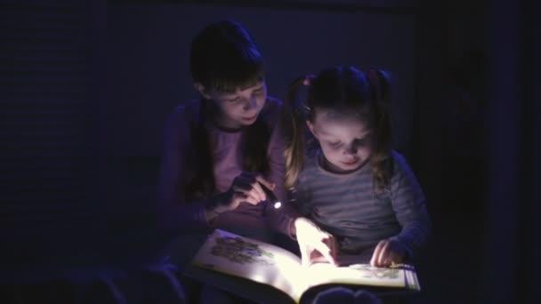 dvě sestry v noci čtou knížku s baterkou v tmavé místnosti
