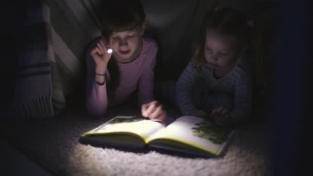 dvě sestry čtou v noci knihu pod přikrývkou s baterkou v tmavé místnosti