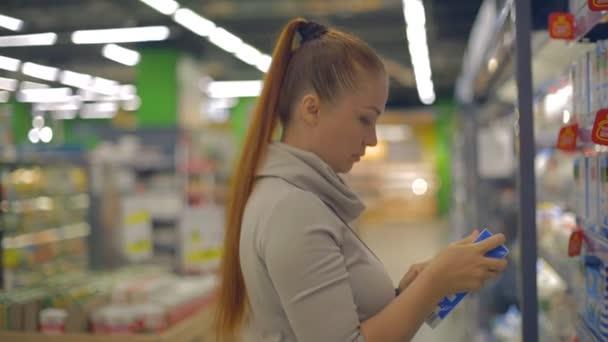 életmód nő választja tejtermékeket a szupermarketben