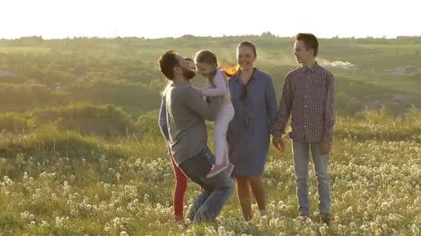 rodiče se třemi dětmi procházky na poli při západu slunce, velká rodina baví společně, koncept rodinného štěstí