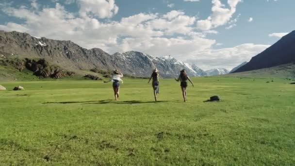Group Of Friends Hold Hands And Run Away From Camera Toward Mountain