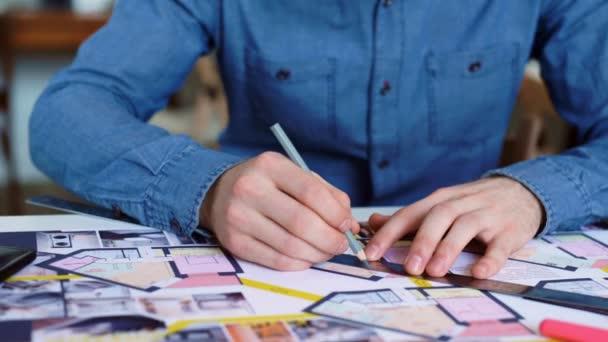 Közelkép: az ember hajlik át az asztalon, és teszi jegyzetek, tollal, az asztalra támaszkodva. Közeli kép: a írásban toll. A mans kezében tartja a tollat, és irányítja a vonal mentén a papír