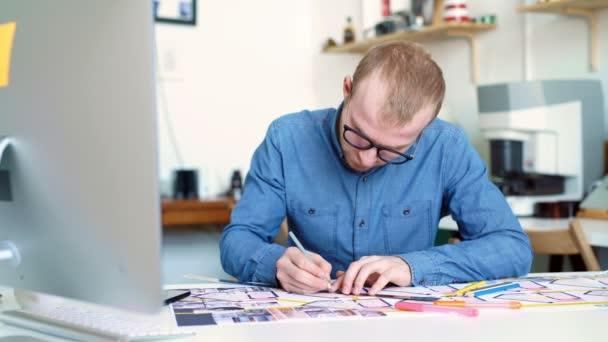 Bokovky inženýr pracuje s blueprint. Střílejte z výše. Mladý inženýr architektonické působení v kanceláři. Vousatý muž v brýlích dělá náčrty. Styl Loft, minimalistický interiér, kresby na stůl