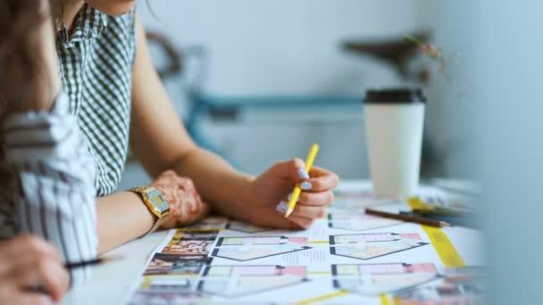Nahaufnahme zweier Architektinnen, die gemeinsam am Schreibtisch Pläne mit Entwürfen diskutieren.