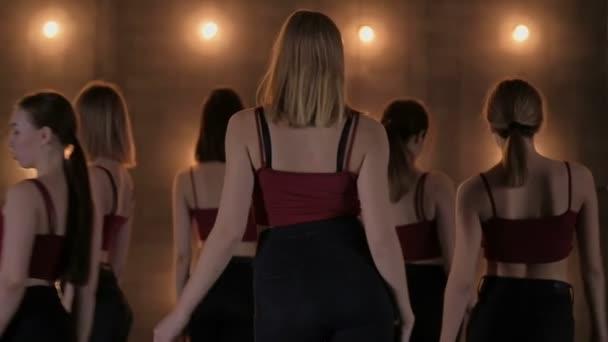 Siluety tančících dívek. go-go tanec. Closeup taneční vystoupení docela ženské skupiny na tmavém pódiu s žluté indikátory. týmu tanec žen na vysokých podpatcích
