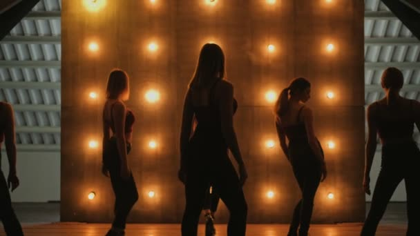 silhouettes of dancing girls. go-go dance. Closeup dance performance of pretty female group on a dark stage with yellow lights. team dance of women in high heels