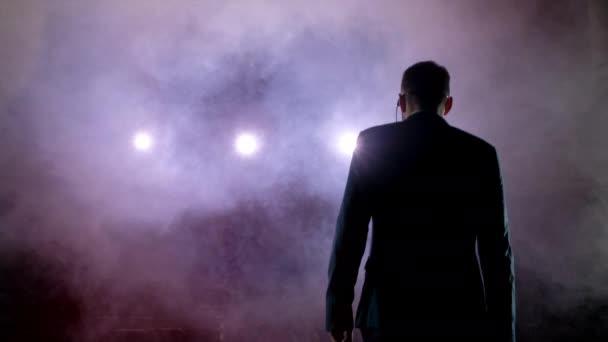 Showman. Fiatal férfi előadóművész, műsorvezető, vagy színész a színpadon. Hát, karok, oldalán, füst, háttérben a reflektorfényben.