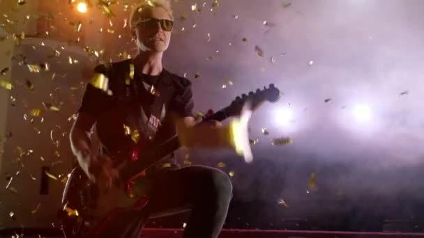 A gitáros fellép. Színpadi fény, füst. A fenti esik arany konfetti