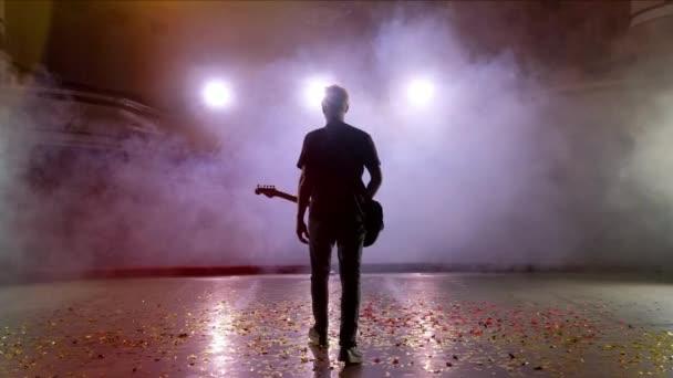 Kytarista se provádí na jevišti. Fázi světlo, kouř.