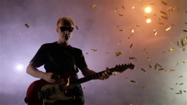 Kytarista se provádí na jevišti. Fázi světlo, kouř. Z výše uvedeného spadají zlaté konfety