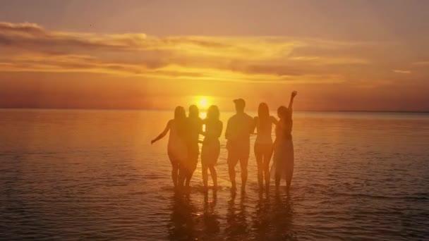 Nagy csoportja barátok-on sunset beach áll. Hétvégi piknik koncepció