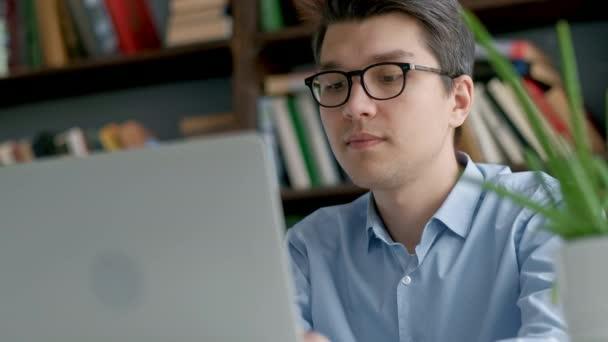 Férfi egyetemi hallgató látszó-on laptop képernyő elgondolkodva rövid idő csinálás a házi feladatot. Vértes koncentrált fiú próbál nehéz feladat teljesítése közben tanul