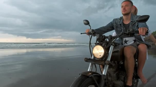 Fiatal szép pár hipszterek lovaglás retro motorkerékpár a strandon, szabadtéri portré, lovaglás srác és lány, utazás együtt, óceán, tenger