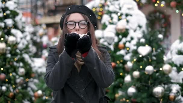 SLOW MOTION: Young woman blowing snow. Young woman blowing snow. Portrait of cute young woman blowing on snow in her hands. Snow scatters in different directions