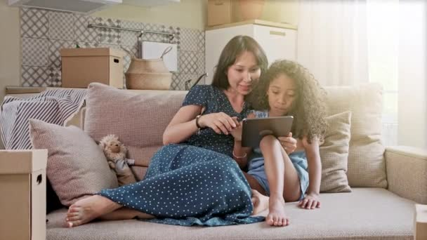 Matka a dcera se baví na digitálním tabletu v domácím interiéru. Roztomilá šťastná matka a dcera používající digitální tablet doma v obývacím pokoji.