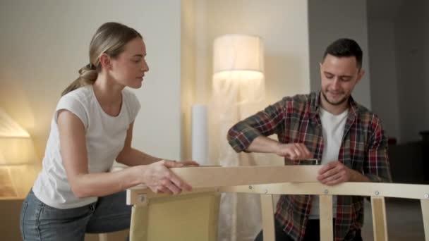 Mladí dospělí se stěhují do nového domova. Pár se stěhuje v sestavování židlí. Mladý mezirasový pár v novém domově. koncepce oprav, rekonstrukcí a osob