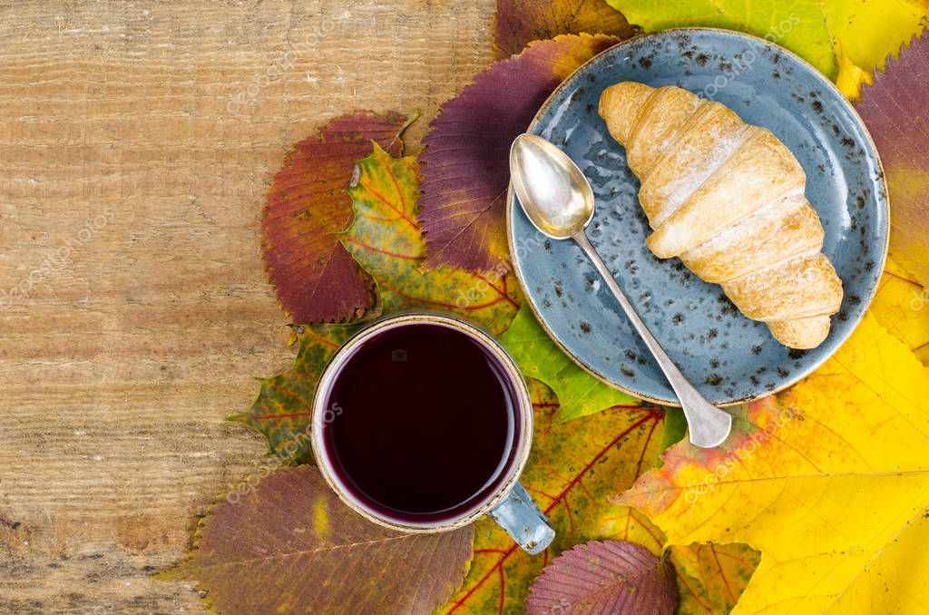 Hot tea, croissant, autumn maple leaves