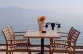 Tavolo in legno e sedie di un caffè di strada sullo sfondo del mare in una giornata di sole estivo