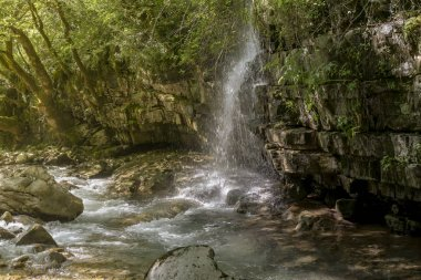 A small waterfall flowing from the mountain in a sunny, summer day (region Tzoumerka, Greece, mountains Pindos).