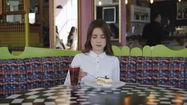 Hezká mladá dívka pije džus a jí chutný zákusek v café 4k